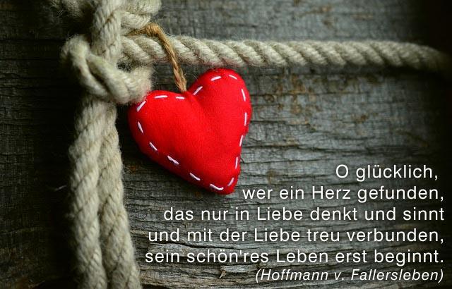 Ein rotes Filzherz am Seil auf Holz, mit Liebesgedicht